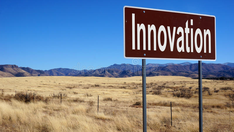 Innovation brown road sign. With blue sky and wilderness stock photos