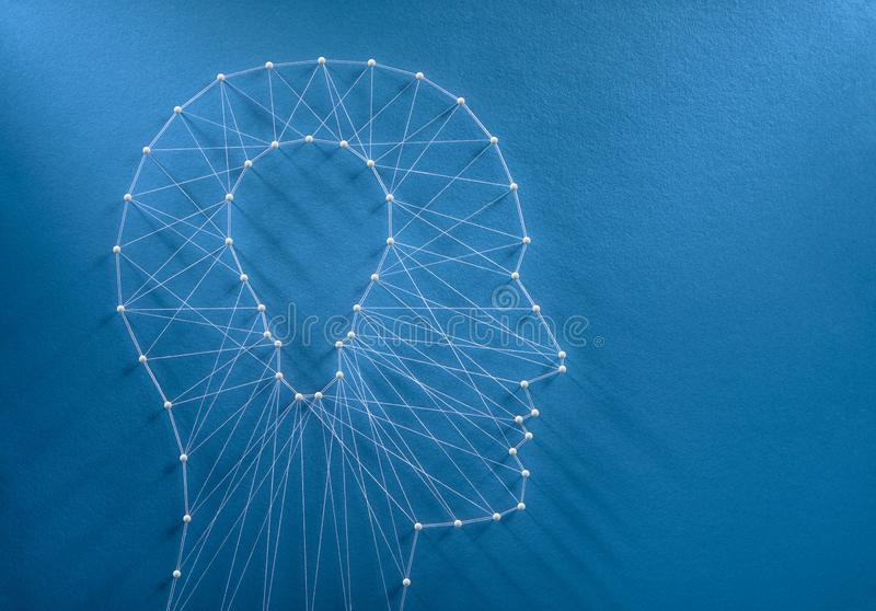 Innovation and creativity concept. Inspiration concept. Network of pins and threads in the shape of a cut out light bulb inside a human head symbolising creative stock photos