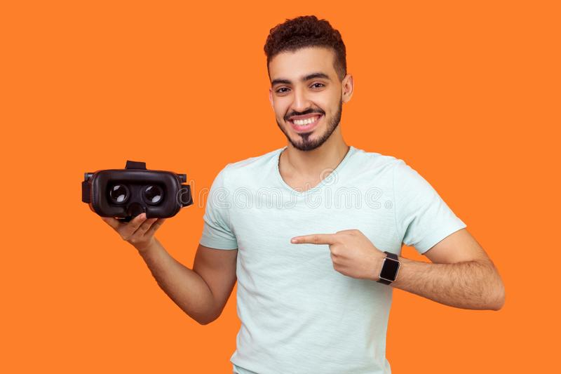Innovation and cyberspace. Portrait of happy brunette man pointing at virtual reality headset. indoor studio shot isolated on royalty free stock photography