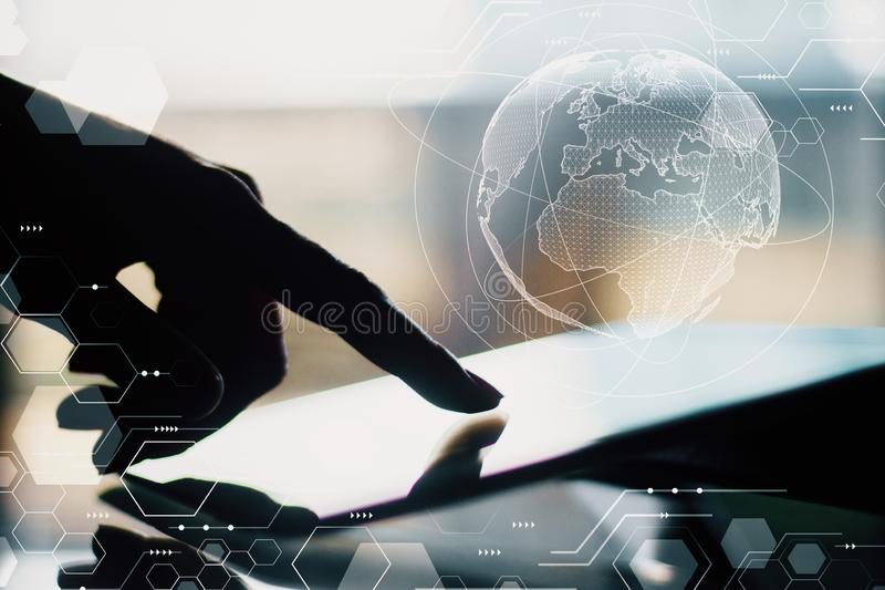 Innovation and distributed concept. Side view of backlit female hands using tablet with glowing globe hologram. Innovation and distributed concept. Double royalty free stock photo
