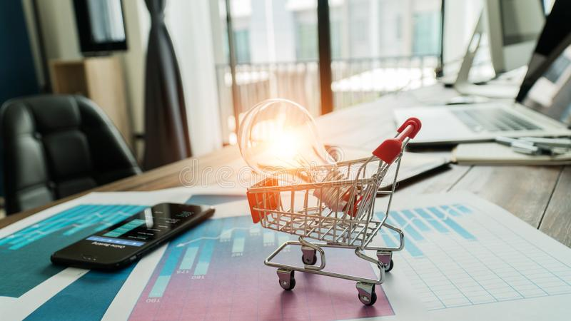 Innovation and inspiration concept,  abstract symbol. Light bulb glowing in shopping cart on business report sales data royalty free stock images