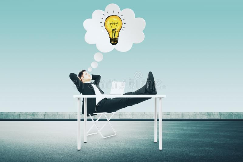 Innovation and solve concept. Relaxing young businessman at desk thinking about bright idea on rooftop city background. Innovation and solve concept royalty free stock photos