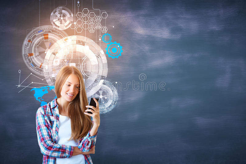 Innovation and technology. Smiling young woman using smartphone on chalkboard background with digital business hologram. Innovation and technology concept royalty free stock images