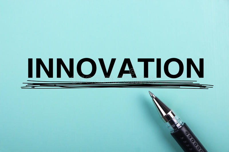 Innovation. Text is on blue paper with black ball-point pen aside royalty free stock image