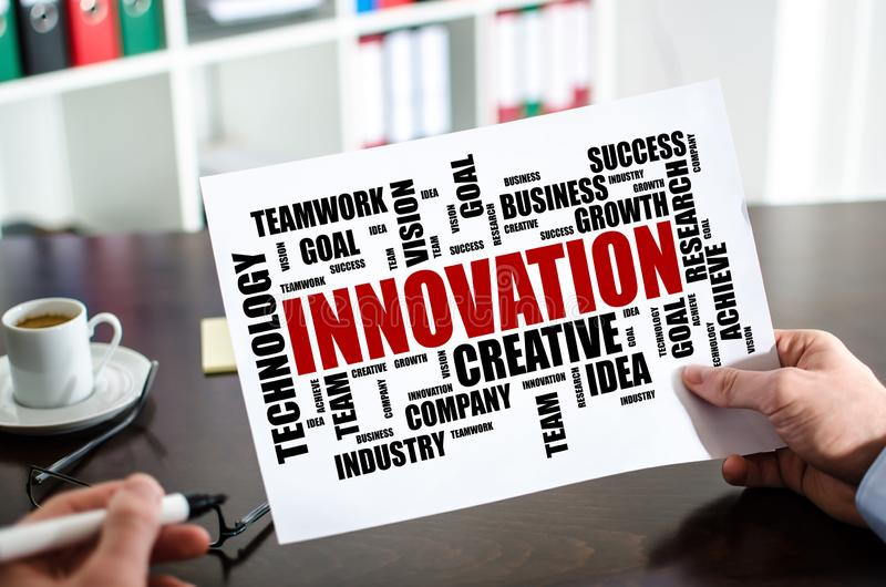 Innovation word cloud concept on a paper. Hand holding a paper showing innovation word cloud concept stock photos