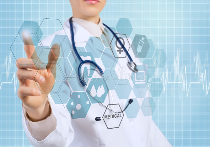Innovative technologies in medicine. Young female doctor touching icon of media screen stock image