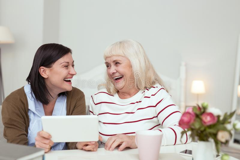 Cheerful elder woman and caregiver playing on tablet. Innovative technology. Positive elder women and caregiver using tablet while laughing stock photos