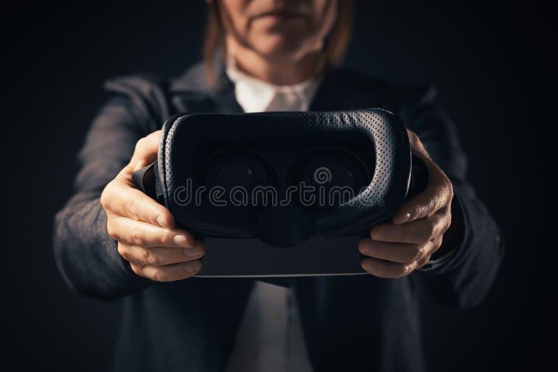 Innovatore della donna di affari che offre la cuffia avricolare degli occhiali di protezione di VR fotografia stock