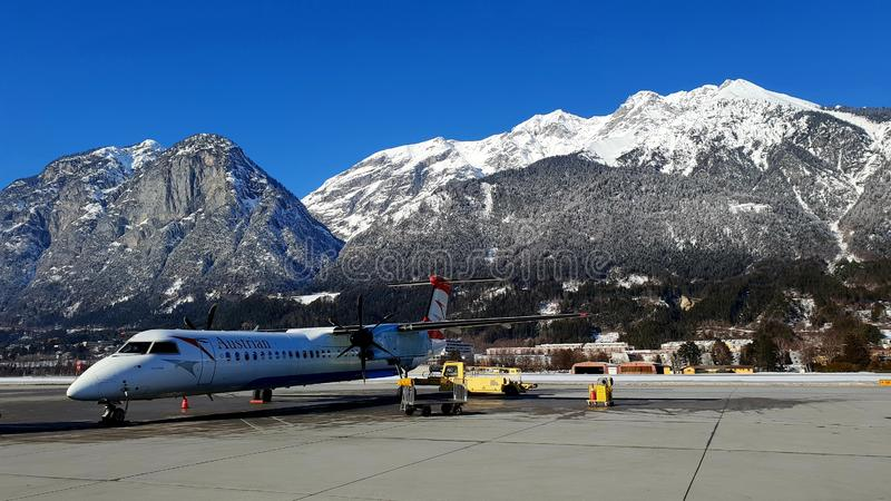 Innsbruck Airport aircraft. Austrian Airlines plane parked on the apron at the Innsbruck Airport in Austria, against a mountain and blue sky background royalty free stock images