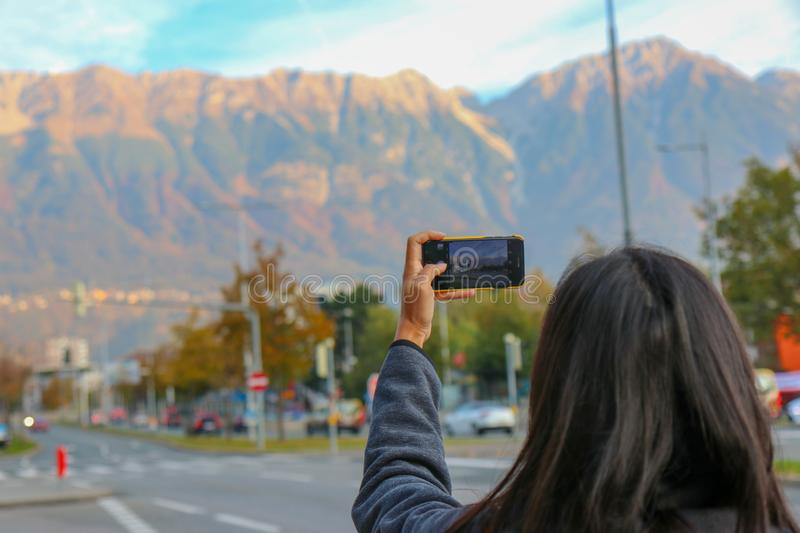 Young traveler on the holiday. Photographer with camera photoshooting from open window of the train in Innsbruck, Austria. Innsbruck, Austria - Oct 18, 2018 royalty free stock photo