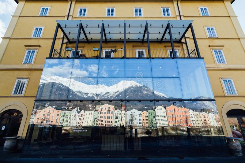 INNSBRUCK, OOSTENRIJK - DECEMBER 2018: weerspiegeling van de bergketen en de huizen van Alpen in het venster royalty-vrije stock afbeelding