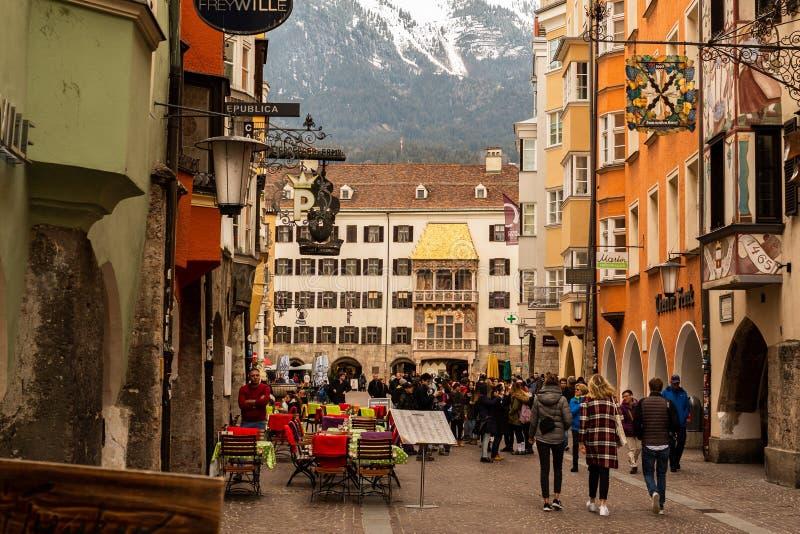 Innsbruck, Tirol/Áustria - 27 de março de 2019: Rua de compra ocupada e o telhado dourado famoso na distância imagens de stock