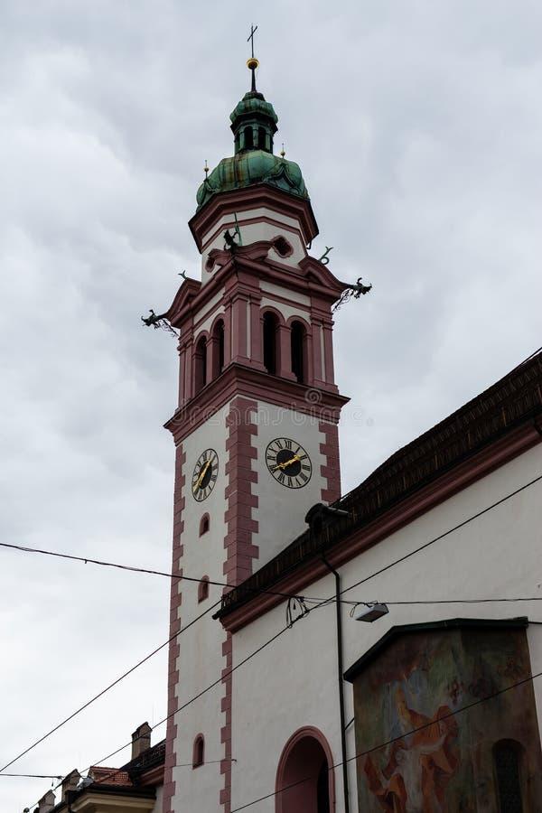 Innsbruck, Tirol/Áustria - 27 de março de 2019: Torre de igreja com cores brancas e cor-de-rosa imagem de stock royalty free