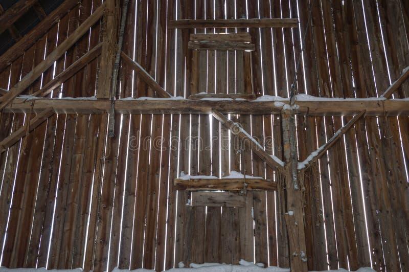 Inom av en gammal ladugård med strålar och lodlinjebräden och snö royaltyfri bild