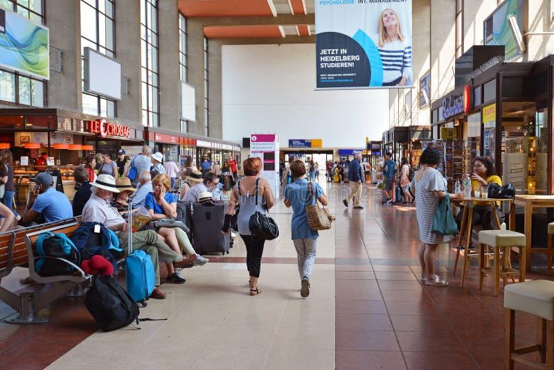 Inom av Heidelberg den huvudsakliga stationen med litet shoppar och kaféer med gå och väntande handelsresande arkivbilder