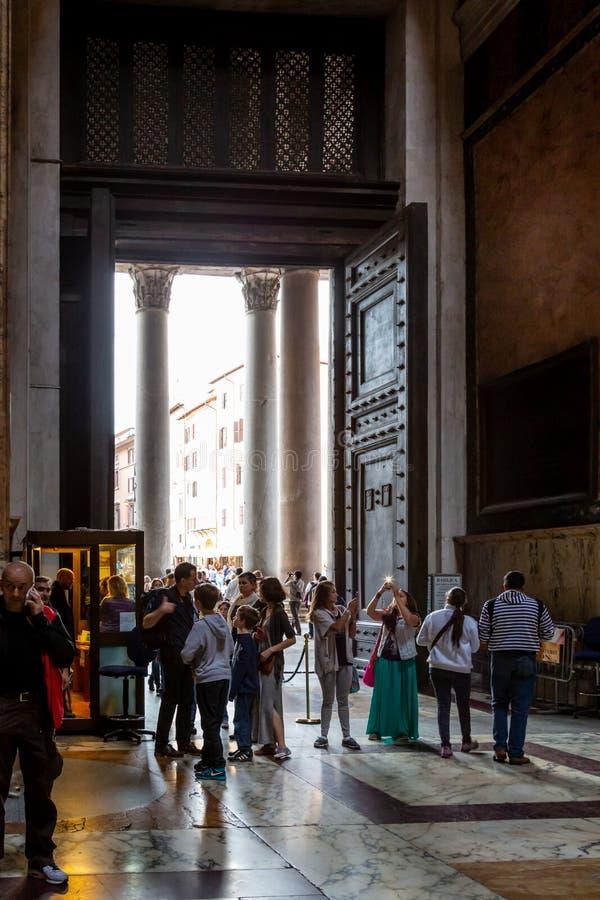 Inom sikt av folk bredvid den stora ingångsdörren på den berömda panteonbyggnaden i Rome royaltyfria bilder