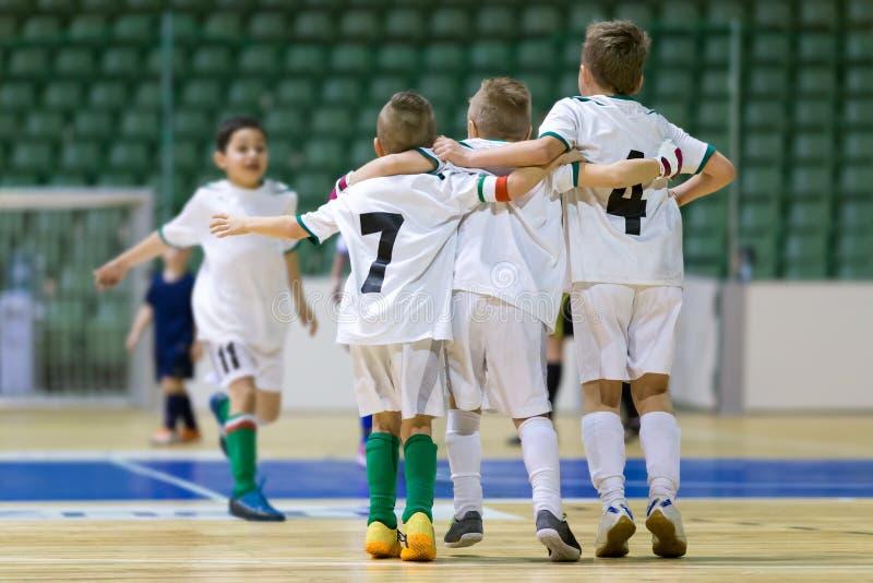Inomhus fotbollfotbollsmatch för barn Lyckliga ungar tillsammans efter vinnande futsal lek Chldren firar sportseger Ungdom s fotografering för bildbyråer