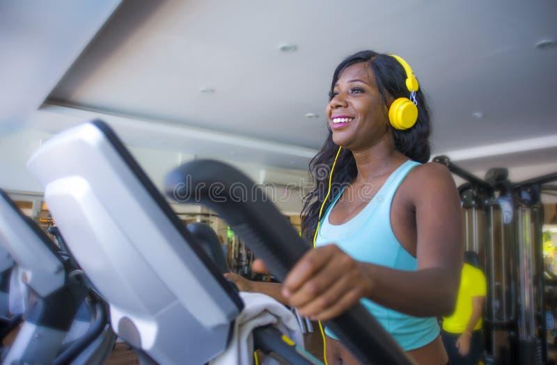 Inomhus idrottshallstående av den unga attraktiva och lyckliga svarta afrikansk amerikankvinnan med hörlurar som utbildar ellipsf royaltyfri foto