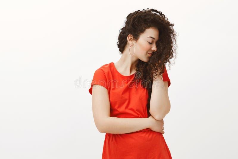 Inomhus skott av den blyga mjuka kvinnlign, i stilfull tillfällig röd klänning, roterande rätt och att le i huvudsak, medan tryck royaltyfri bild