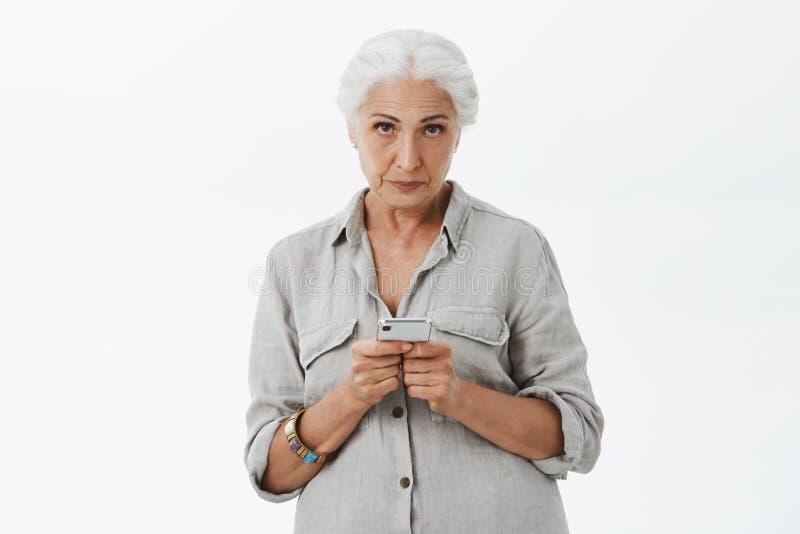 Inomhus skott av den lugna och allvarlig-seende irriterade höga kvinnan med grått hår som ser med föraktformen under pannan arkivfoto