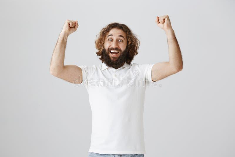 Inomhus skott av den lyckliga tillfredsställda östliga mannen med lockigt hår och skägget som lyfter nävar upp i triumf som firar royaltyfri fotografi