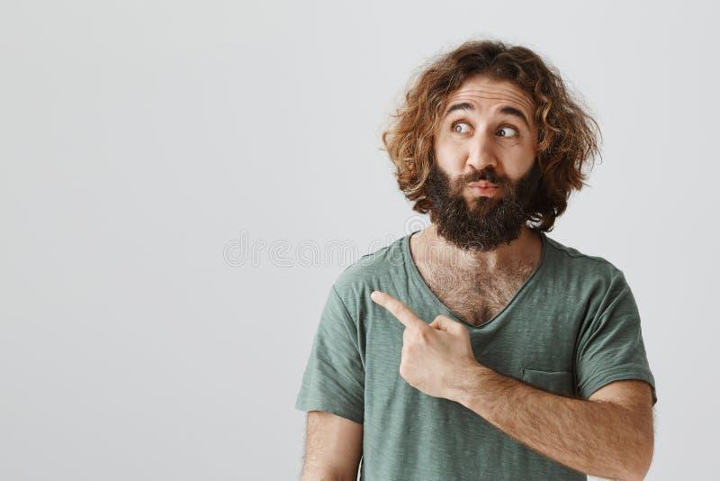 Inomhus skott av den nyfikna och intresserade stiliga östliga mannen med att peka för lockigt hår som och för skägg lämnas med fö royaltyfria foton