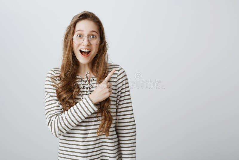 Inomhus skott av den positiva attraktiva caucasian kvinnliga studenten i moderiktiga exponeringsglas som pekar på det övre högra  arkivbild
