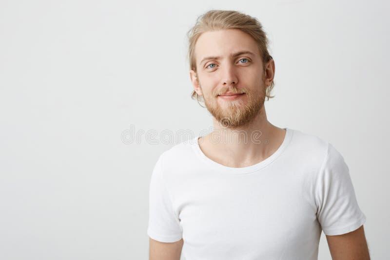 Inomhus skott av den positiva snygga caucasian blonda mannen med skägget och mustaschen som smilar, medan se kameran och royaltyfria bilder
