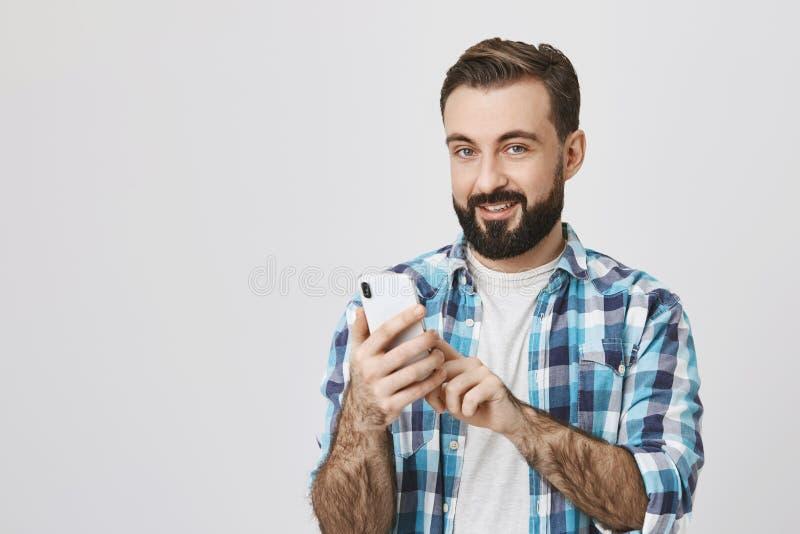 Inomhus skott av den stiliga grabben med moderiktig frisyr som bläddrar nätverket i smartphone, medan se och le glatt på royaltyfri bild