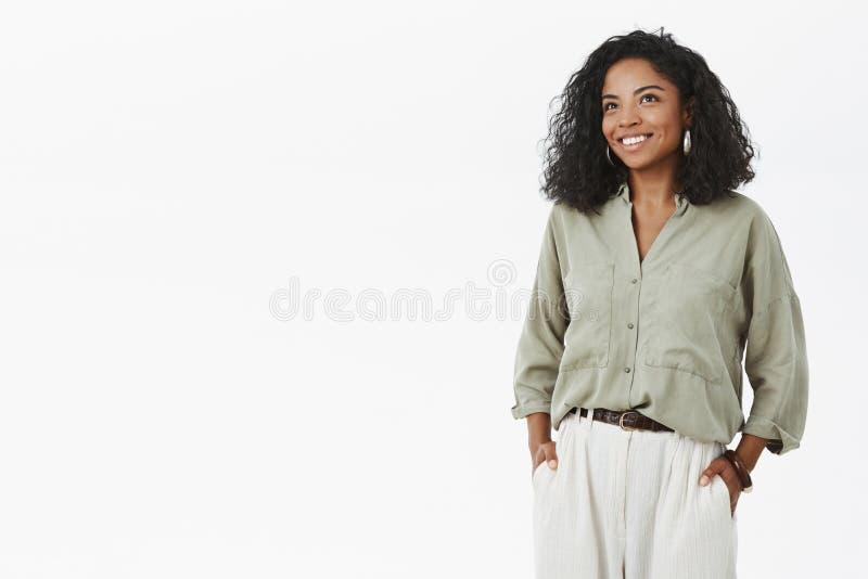 Inomhus skott av det kvinnliga entreprenör- och mammaanseendet för lyckad snygg afrikansk amerikan i stilfull hucky skjorta och royaltyfri fotografi
