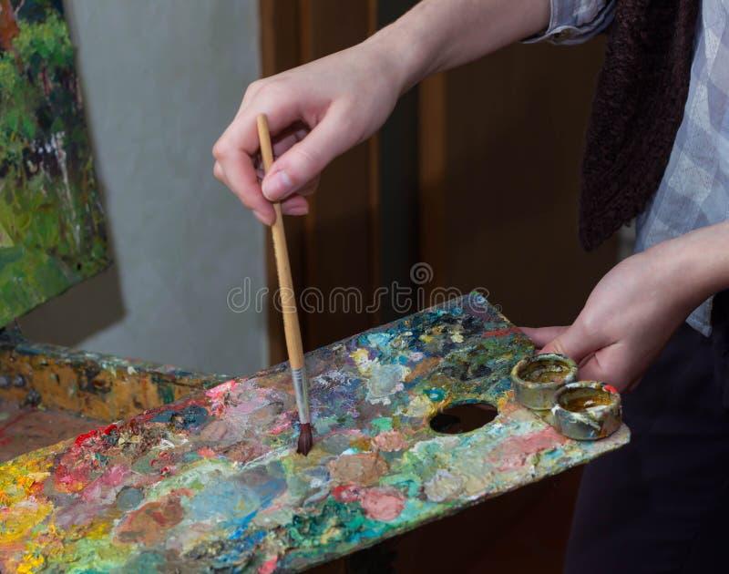 Inomhus skott av yrkesmässig kvinnlig konstnärmålning på kanfas i studio arkivfoto