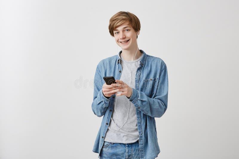 Inomhus stående av den europeiska blonda grabben med blåa ögon i messaging för mobiltelefon för grov bomullstvillskjorta hållande arkivbild