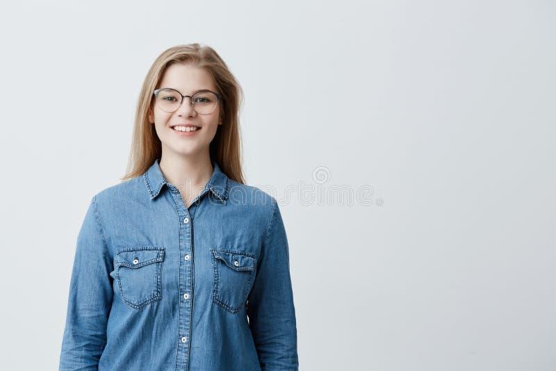 Inomhus stående av den härliga blonda unga europeiska kvinnan med rakt hår, bärande stilfullt glasögon som ler royaltyfri bild