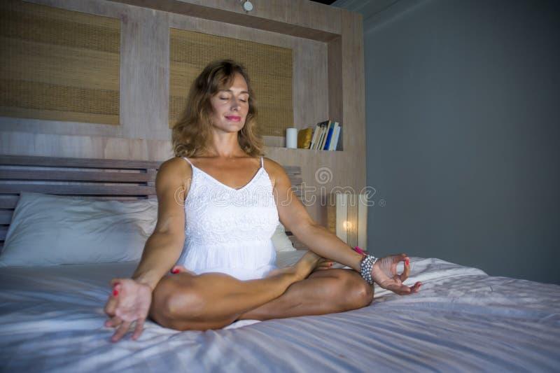 Inomhus stående av den härliga och färdiga sunda kvinna30-tal som öva yoga, i att posera för säng som är lugna, och avkopplat som royaltyfria bilder