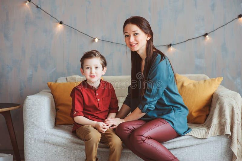 inomhus stående av den lyckliga älska modern som hemma tröstar litet barnsonen royaltyfri foto