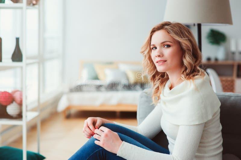 inomhus stående av den unga själviska härliga kvinnan som hemma tycker om vintertid arkivbild