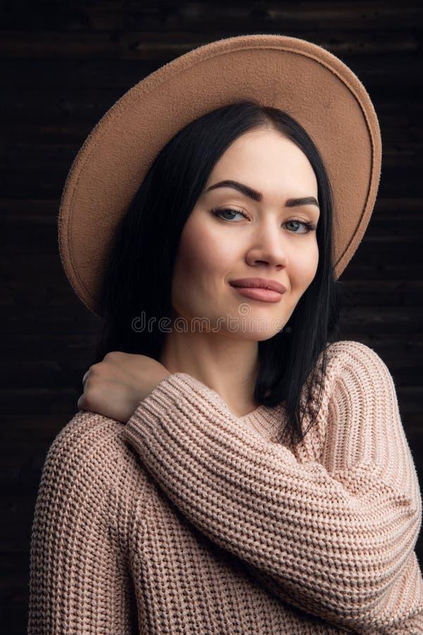Inomhus stående av en ung härlig hatt och en sweather för trendig kvinna bärande arkivbild