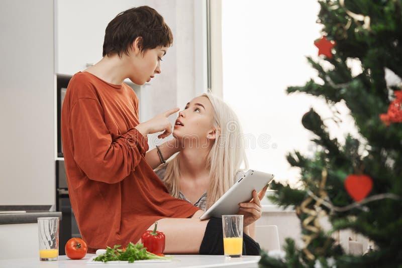 Inomhus stående av unga sinnliga och mjuka par av flickor som uttrycker förälskelse och dragningen, medan sitta i kök och arkivfoton