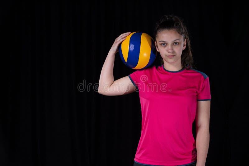 Inomhus ung volleybollkvinnaspelare som isoleras på mörk bakgrund royaltyfri fotografi