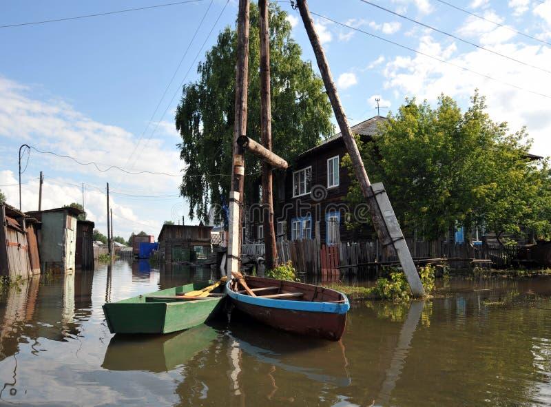 Inondazione Il fiume Ob', che è emerso dalle rive, ha sommerso le periferie della città Barche vicino alle case dei residenti fotografia stock libera da diritti