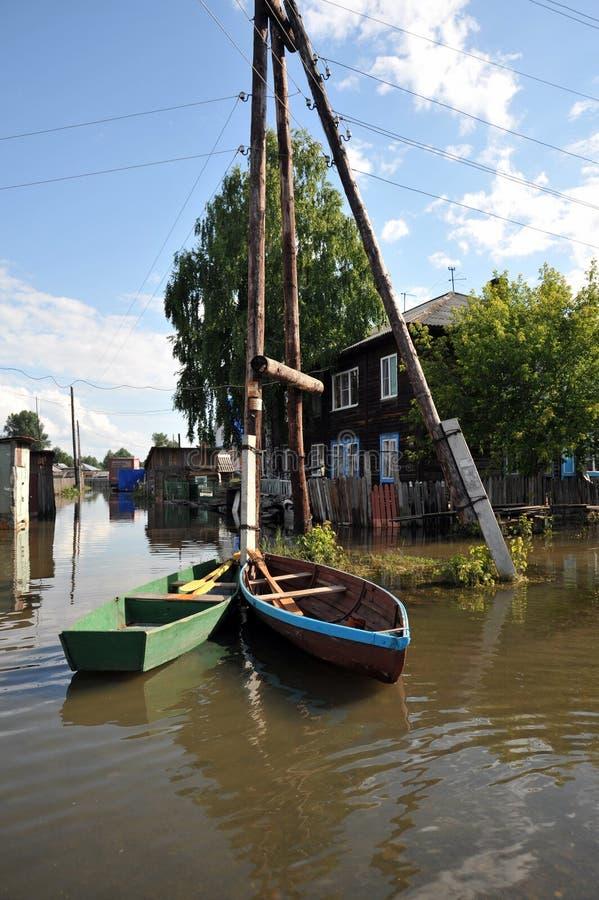 Inondazione Il fiume Ob', che è emerso dalle rive, ha sommerso le periferie della città Barche vicino alle case dei residenti immagini stock