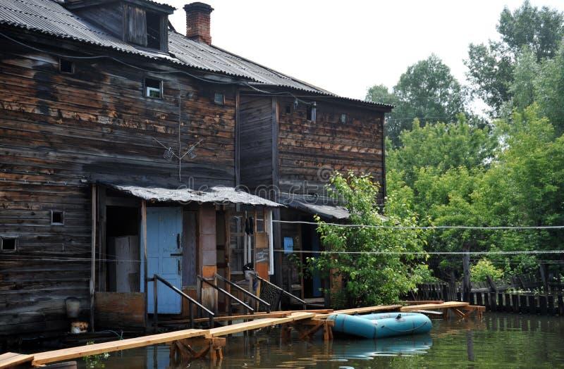 Inondazione Il fiume Ob', che è emerso dalle rive, ha sommerso le periferie della città Barche vicino alle case dei residenti fotografie stock