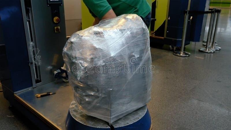 Inpackning av bagagebagagepåsen på flygplatsterminalen royaltyfria foton