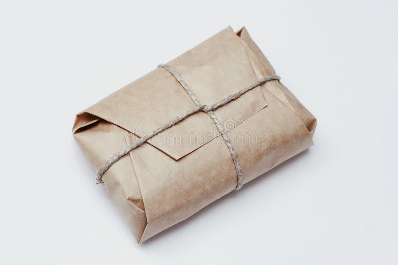 Inpackning av den bruna hantverkpapperspacken med hampa som gåva Handen - gjorde jordlottpåsegåvan bakgrund isolerad white royaltyfri bild