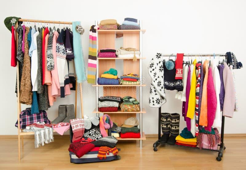 Inpackning av resväskan för vintersemester Garderob med utmärkt ordnad kläder och ett fullt bagage arkivfoton
