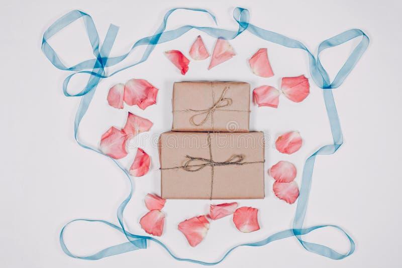 Inparchment de deux présents avec les pétales roses et ruban bleu sur le fond blanc Vue supérieure, configuration plate images stock