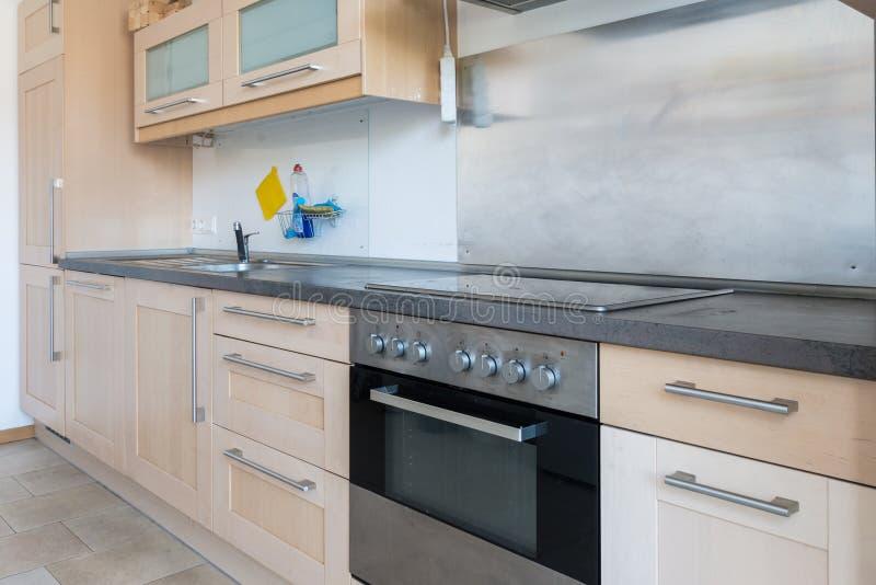 Inpassat kök i en lägenhet med elektriska anordningar och worktop och enheter och väggskåp royaltyfri fotografi