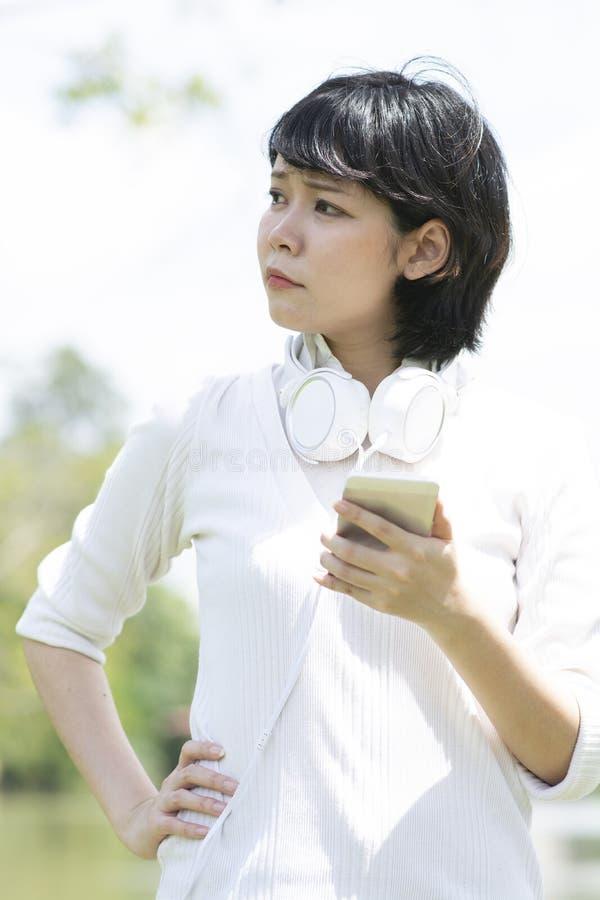 Inqui?ter la femme asiatique faisant l'appel t?l?phonique dans le jardin photos libres de droits