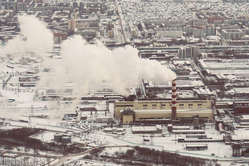 Inquinamento atmosferico da fumo che esce da due camini della fabbrica Zona industriale nella città immagine stock