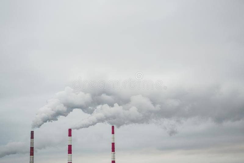 Inquinamento atmosferico ed ambientale, concetto ecologico di problemi Fumo dai camini della fabbrica contro un cielo nuvoloso gr fotografia stock